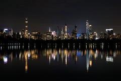 Ljus av den Manhattan horisonten som reflekterar i en sjö i Central Park nya USA york royaltyfri foto
