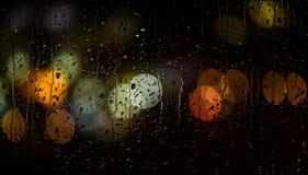 Ljus av girlanden som är suddiga på svart bakgrund bakgrundsbegrepp Tänder defocused behind vått exponeringsglas med droppar av v Arkivbild