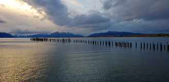 Ljus av solnedgången över restna av pir, Puerto Natales, Chile royaltyfria foton