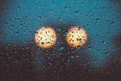 Ljus av två lyktstolpar bak det regniga fönstret royaltyfria bilder