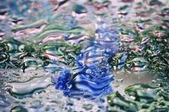 Ljus bakgrundstextur för abstrakt vår med det våta fönstret, suddiga regndroppar, droppar av vatten på exponeringsglas, som vatte Royaltyfria Foton
