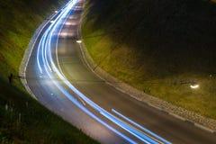 Ljus ljus bana från bilar Nattlandskap på lång exponering Röda och blåa ljus royaltyfri foto