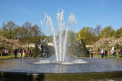 Ljus blå himmel över fontain för vattenpöl i vårtid i Keukenhof blommaträdgård Det lyckliga folket som in går, parkerar fotografering för bildbyråer