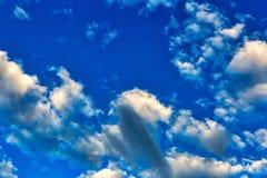 Ljus blå himmel med pösiga spridda moln Arkivbilder