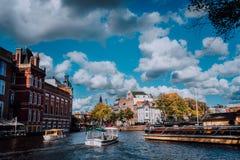 Ljus blå himmel och fluffiga moln över Amstel i Amsterdam Nederländerna, för stadsvår för gränsmärke gammalt europeiskt landskap  royaltyfri foto