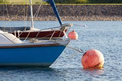 Ljus blå segelbåt på en förtöja boll Arkivbild