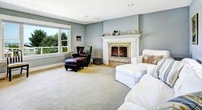 Ljus - blå vardagsrum med den vita soffan och spisen Royaltyfria Foton
