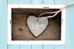 ljus - blått färgad ram- och stenhjärta med ordförälskelsen Royaltyfri Bild