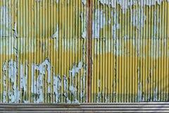 Ljus - blått- och gulingmålarfärg med skrapan på det galvaniserade järnet Arkivbild
