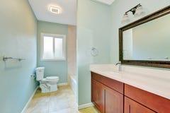 Ljus - blått omdanat badrum med träfåfängakabinettet Royaltyfri Bild