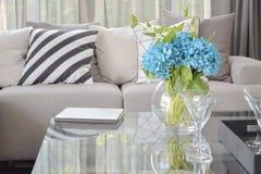 Ljus - blåa blomma- och vinexponeringsglas på mitttabellen med randiga svartvita kudde- och grå färgsignalkuddar på den beigea so Royaltyfri Foto