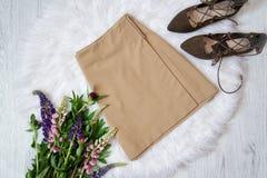 Ljus - brun mockaskinnkjol och skor på vit päls, en bukett av blommor trendigt begrepp Fotografering för Bildbyråer