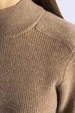 Ljus - brun woolen stucken sweater på kvinnlig kropp för ` s för closeupeyedroppers hög för upplösning sikt mycket royaltyfri foto