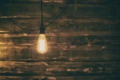 Ljus Edison kula på mörk träbakgrund fotografering för bildbyråer