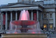 Ljus exponerar vattnet i en av springbrunnarna på Trafalgar Square, Westminster, London, UK på skymning royaltyfri fotografi