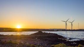 Ljus färgad kulör solnedgång med väderkvarnar i Corralejo, Fue Royaltyfri Bild