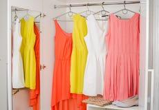 Ljus färgrik klänning som hänger på laghängare Arkivfoto