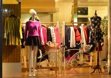 Ljus för lagerskyltfönstret och den dekorativa cykeln, modeboutiqueskyltfönstret med skyltdockor, lagerförsäljningsfönstret, fram Royaltyfri Fotografi