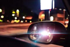 Ljus för polisbil reflekterade på backspegeln av ett parkerat c arkivfoto