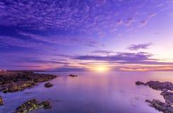 Ljus förträfflig ljus solnedgång och stenig seacost Arkivbild