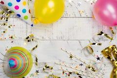 Ljus festlig karnevalbakgrund med hattar, banderoller, konfettier och ballonger på vit bakgrund Arkivbilder