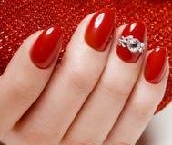 Ljus festlig röd manikyr på kvinnliga händer Spikar design Royaltyfri Bild