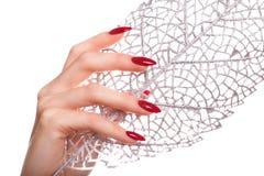 Ljus festlig röd manikyr på kvinnliga händer Spikar design arkivbild
