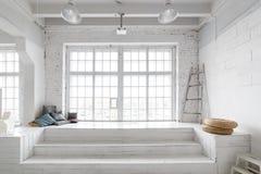 Ljus fotostudioinre med det stora fönstret, högt tak, vitt trägolv Arkivfoto