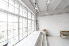 Ljus fotostudioinre med det stora fönstret, högt tak, vitt trägolv Arkivbilder