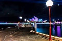 Ljus gångbana med operahuset i natt royaltyfri foto