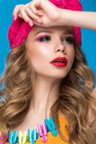 Ljus gladlynt flicka i hem- hatt, färgrikt smink, krullning och rosa manikyr Härlig le flicka royaltyfri bild