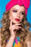 Ljus gladlynt flicka i hem- hatt, färgrikt smink, krullning och rosa manikyr Härlig le flicka royaltyfri foto