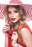 Ljus gladlynt flicka i sommarhatt, färgrikt smink, krullning och rosa manikyr Härlig le flicka fotografering för bildbyråer