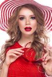 Ljus gladlynt flicka i sommarhatt, färgrikt smink, krullning och rosa manikyr Härlig le flicka arkivbilder
