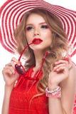 Ljus gladlynt flicka i sommarhatt, färgrikt smink, krullning och rosa manikyr Härlig le flicka arkivfoton