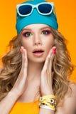 Ljus gladlynt flicka i sporthatt, färgrikt smink, krullning och rosa manikyr Härlig le flicka arkivbild