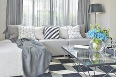 Ljus - grått L formsoffauppsättning med varierar modell- och färgkuddar i vardagsrum arkivfoton