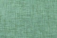 Ljus - grön textilbakgrundscloseup Struktur av tygmakroen royaltyfria foton