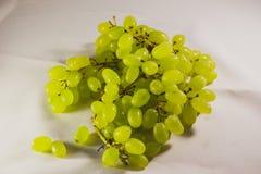 Ljus - gröna druvor på den vita torkduken royaltyfria foton