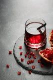 Ljus granatröttdrink och en sur röd granatäpple på ett ljus - grå bakgrund Exotiska ingredienser för sommarcoctailar fotografering för bildbyråer