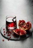 Ljus granatröttdrink och en tropisk granatäpple på ett ljus - grå bakgrund Exotiska ingredienser för sommarcoctailar kopia royaltyfria foton
