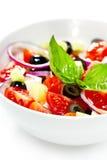 Ljus grekisk sallad med nya grönsaker som garneras med basilika. Royaltyfri Fotografi