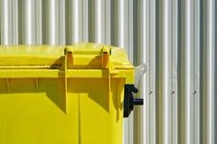Ljus gul dumpster mot en vit industriell korrugerad sid för cladding eller för vägg royaltyfri foto