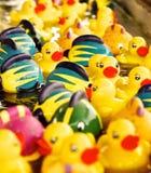 Ljus gul Rubber Duckies och färgfisk som svävar i en ström av vatten i ett karnevallekbås Arkivfoton