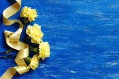 Ljus - gula nejlikor med det gula siden- bandet Fotografering för Bildbyråer