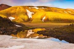 Ljus guld- gryning exponerar bergen och glaciärerna Arkivfoto