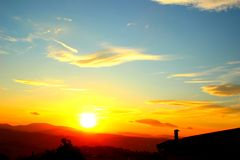Ljus guling-blått himmel med inställningssolen arkivfoto