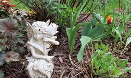 Ljus guling och den röda tulpan bak den vita murbrukfen med annan gör grön i vårträdgårdsäng Royaltyfri Fotografi