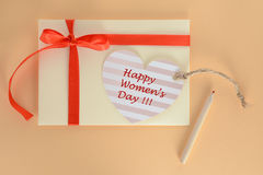 Ljus - gult kuvert med ett rött för kvinnadag för band och för hjärta lyckligt kort på en aprikosbakgrund Royaltyfria Foton