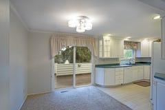 Ljus hemmiljö med vit kökcabinetry fotografering för bildbyråer